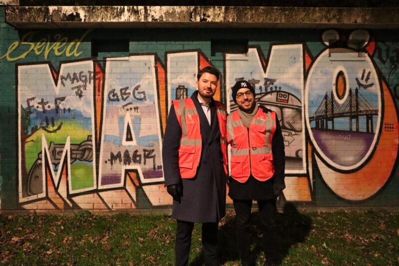 Två personer framför graffitti i Sofielund