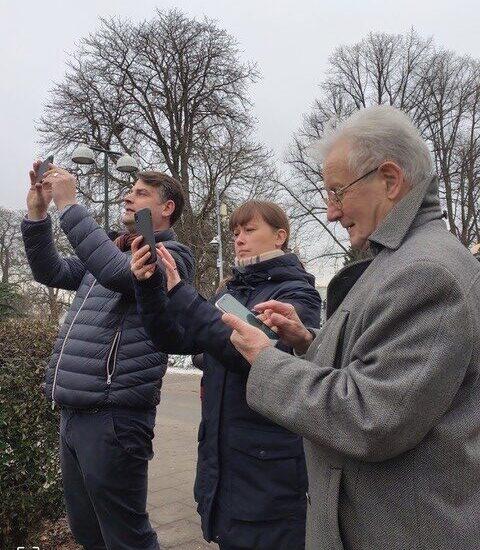 Tre personer utomhus, med mobiltelefonerna i högsta hugg